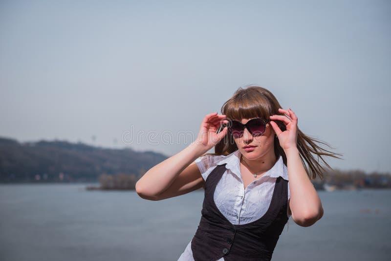 Mujeres que sostienen las gafas de sol con el pelo marrón claro, vestido en blanco y negro, el retrato, día soleado, con el río y fotos de archivo