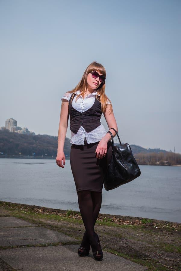 Mujeres que sostienen las gafas de sol con el pelo marrón claro, vestido en blanco y negro, el retrato, día soleado, con el río y fotografía de archivo