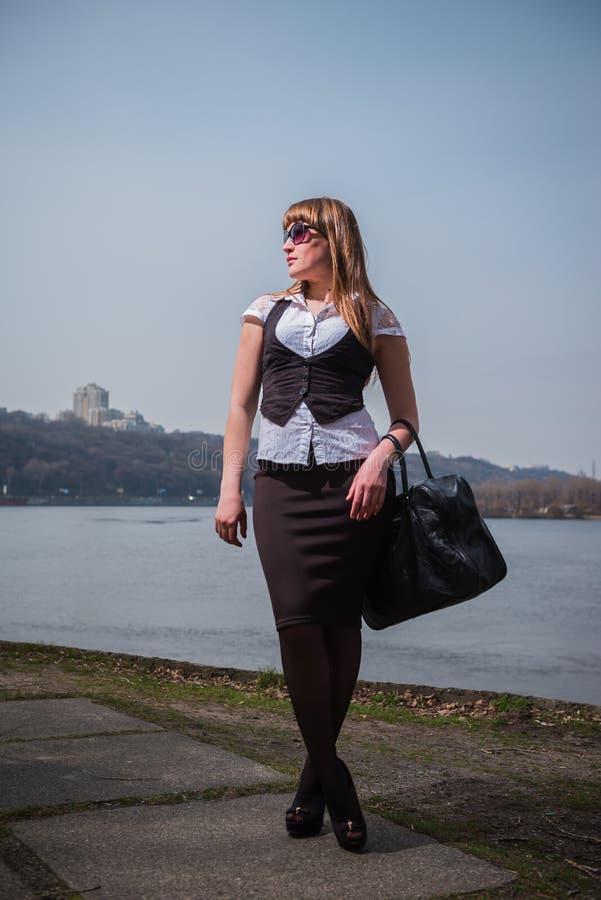 Mujeres que sostienen las gafas de sol con el pelo marrón claro, vestido en blanco y negro, el retrato, día soleado, con el río y imágenes de archivo libres de regalías