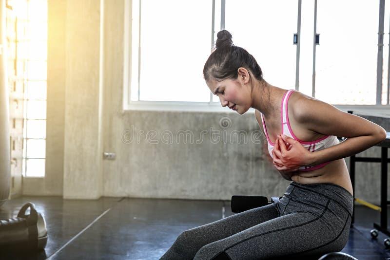 Mujeres que sufren de dolor de pecho Femenino tocando su pecho con las manos mientras que ejercicio Muchacha asi?tica Mujeres her fotos de archivo