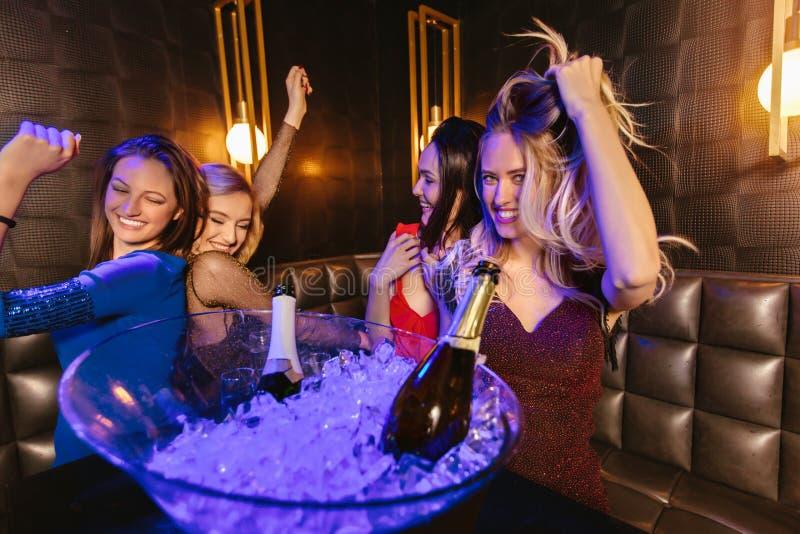Mujeres que tintinean los vidrios del champ?n y que celebran en el club nocturno fotos de archivo libres de regalías