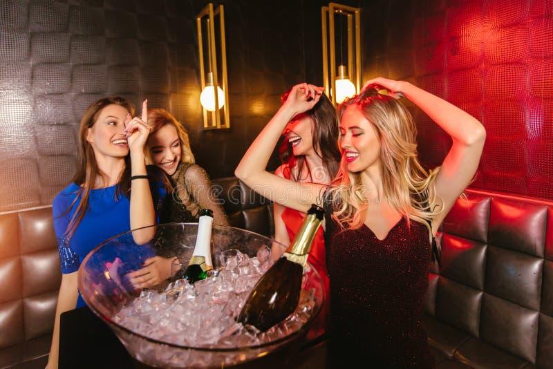 Mujeres que tintinean los vidrios del champ?n y que celebran en el club nocturno foto de archivo libre de regalías