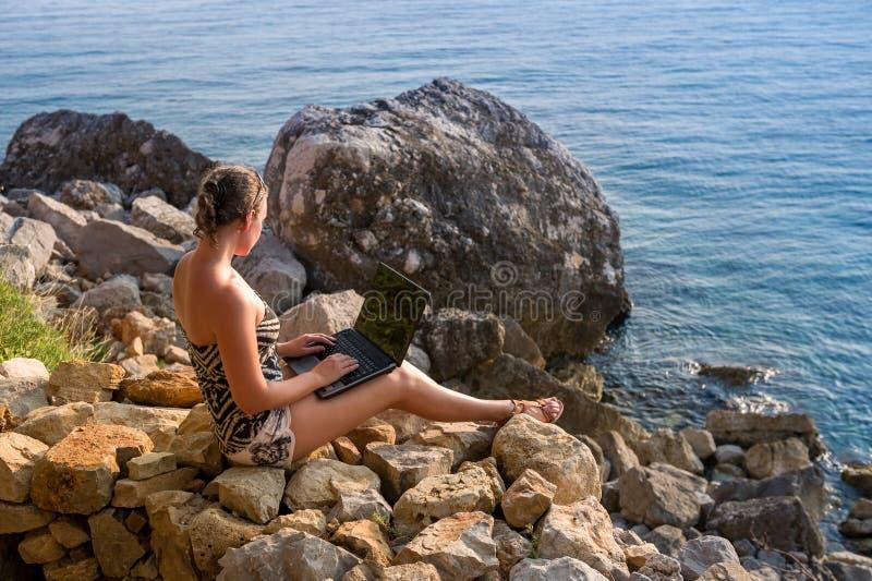 Mujeres que trabajan con el ordenador portátil en la orilla de mar imagen de archivo libre de regalías