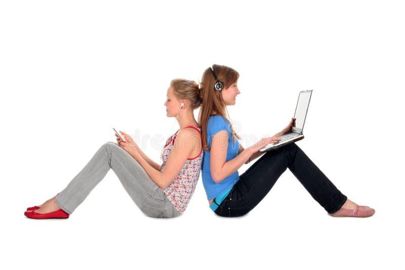 Mujeres que usan la computadora portátil y al jugador MP3 imagen de archivo libre de regalías
