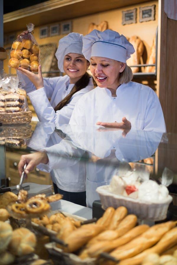 Mujeres que venden los pasteles y los panes frescos fotografía de archivo