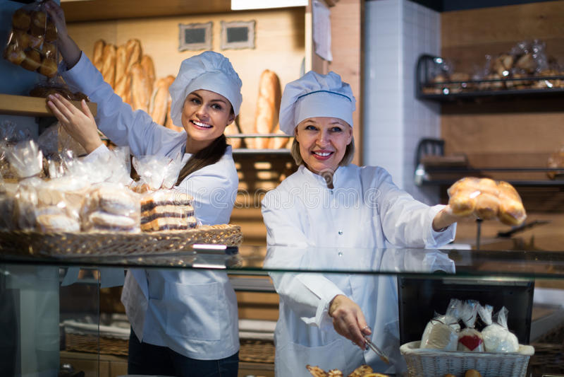 Mujeres que venden los pasteles y los panes frescos foto de archivo