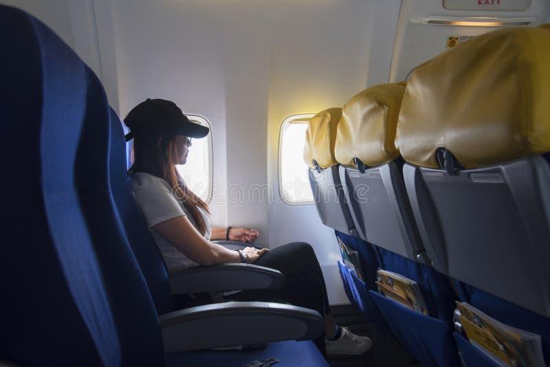 Mujeres que viajan por un aeroplano Mujeres que se sientan por la ventana de los aviones y que miran afuera imagen de archivo