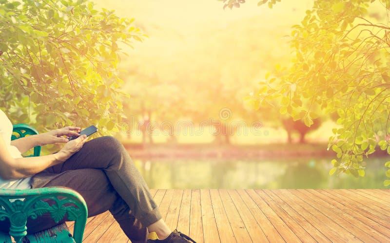 Mujeres relajantes que se sientan en banco usando el teléfono móvil en la puesta del sol fotos de archivo libres de regalías