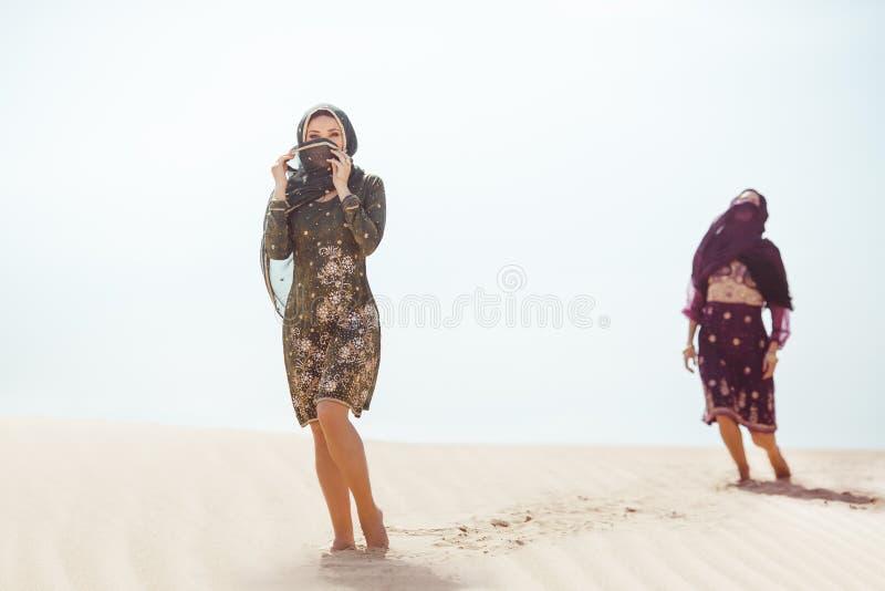 Mujeres sedientas que caminan en un desierto Perdido durante el viaje imagenes de archivo