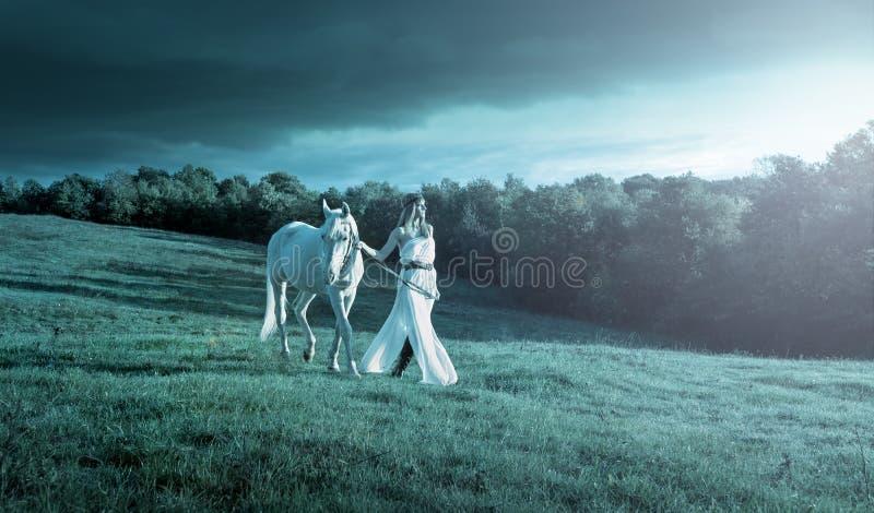 Mujeres sensuales hermosas con el caballo blanco imagen de archivo