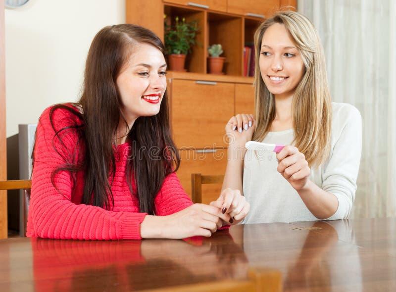Mujeres sonrientes con la prueba de embarazo imagen de archivo