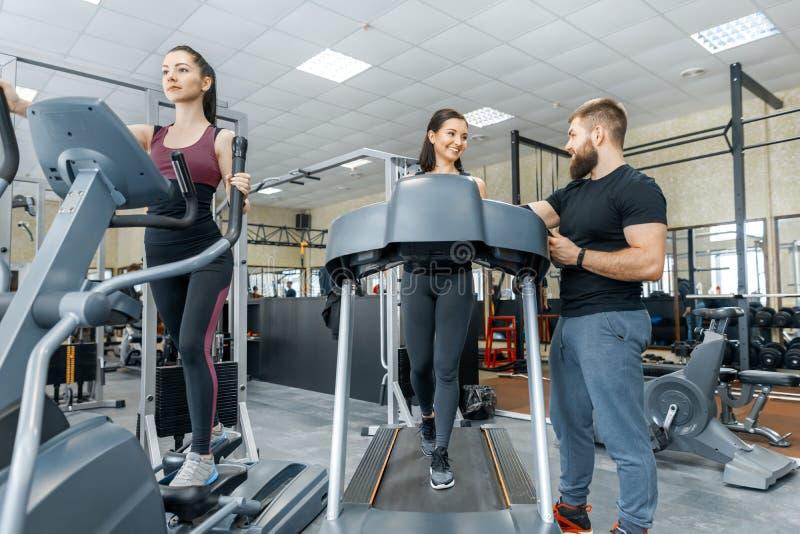Mujeres sonrientes jovenes de la aptitud con el instructor personal un hombre atlético adulto en la rueda de ardilla en el gimnas imagen de archivo