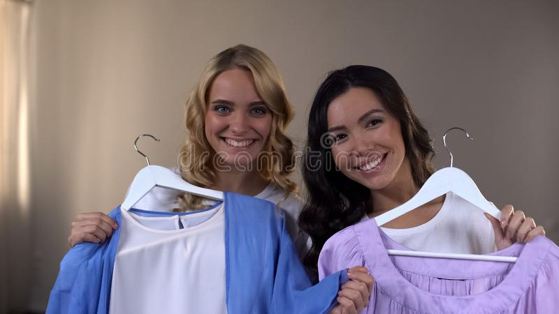 Mujeres sonrientes que eligen la ropa, haciendo compras con el mejor amigo, tiempo libre junto fotografía de archivo libre de regalías