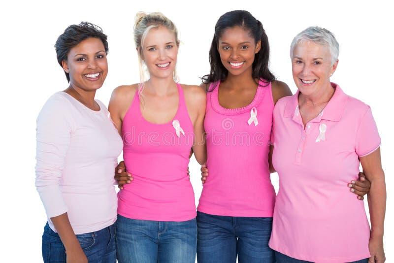 Mujeres sonrientes que llevan cintas rosadas de los tops y del cáncer de pecho foto de archivo libre de regalías