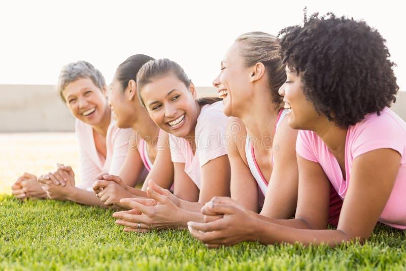 Mujeres sonrientes que mienten en fila y rosa que lleva para el cáncer de pecho imágenes de archivo libres de regalías