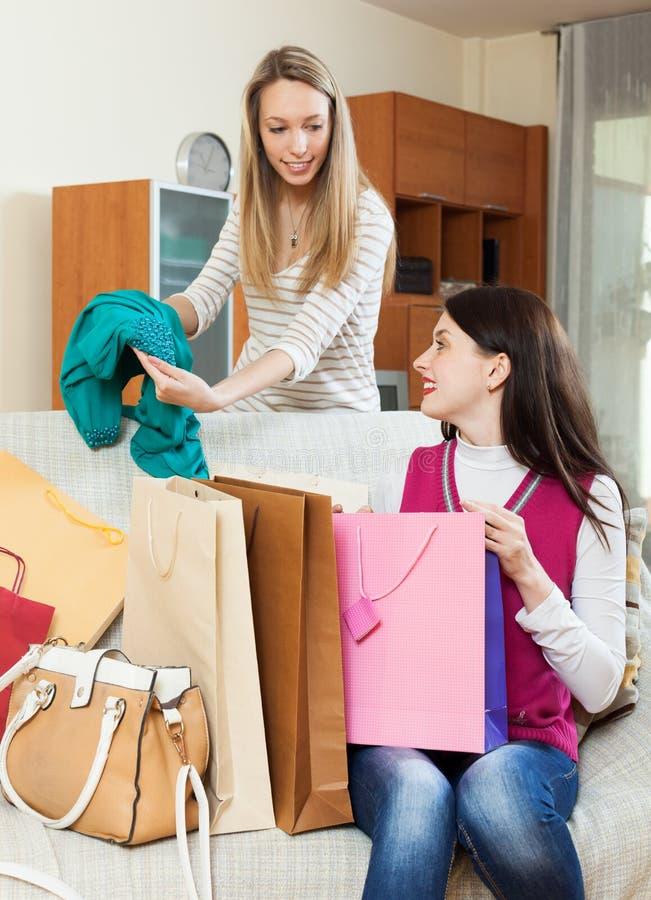 Mujeres sonrientes que miran el nuevo vestido verde imágenes de archivo libres de regalías