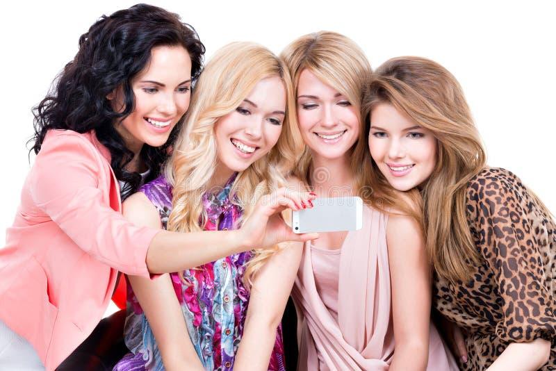 Mujeres sonrientes que miran el teléfono móvil imagenes de archivo
