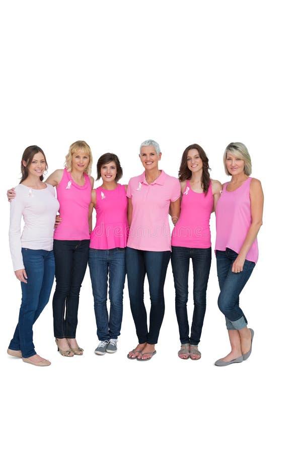 Mujeres sonrientes que presentan con los tops rosados para la conciencia del cáncer de pecho imagenes de archivo