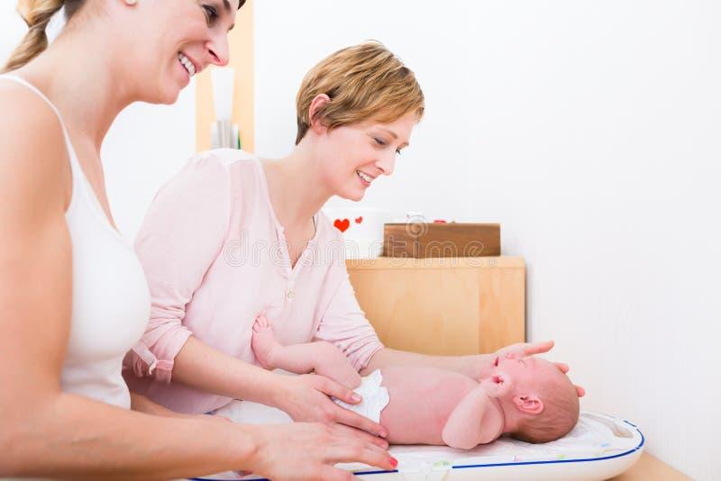 Mujeres sonrientes que toman el cuidado del bebé fotos de archivo