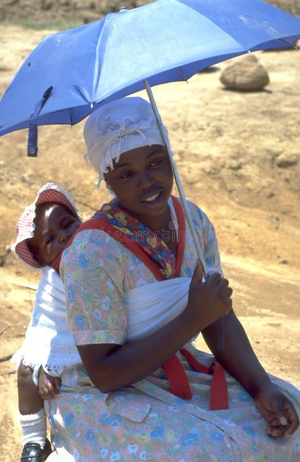 Mujeres surafricanas con su bebé debajo del paraguas imagen de archivo libre de regalías