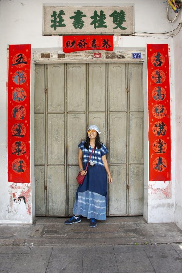 Mujeres tailandesas del viajero que presentan para la foto de la toma con la puerta de madera retra y estilo chino antiguo de la  fotos de archivo