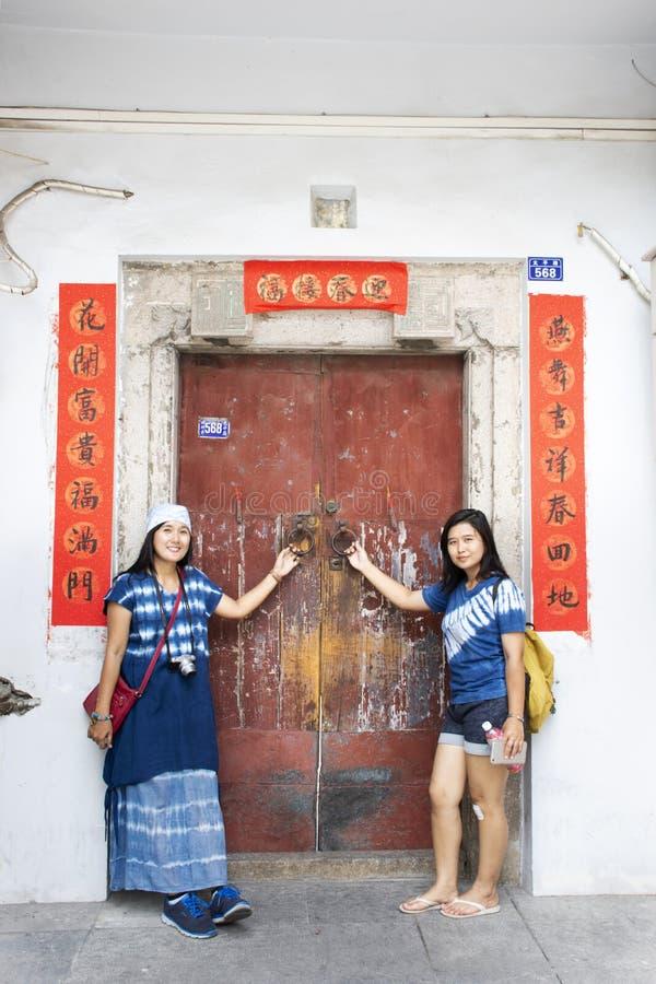 Mujeres tailandesas del viajero que presentan para la foto de la toma con la puerta de madera retra y estilo chino antiguo de la  foto de archivo