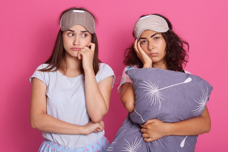 Mujeres trastornadas y cansadas que se unen contra la pared rosada del estudio con expresiones faciales agotadas después de diver imagen de archivo