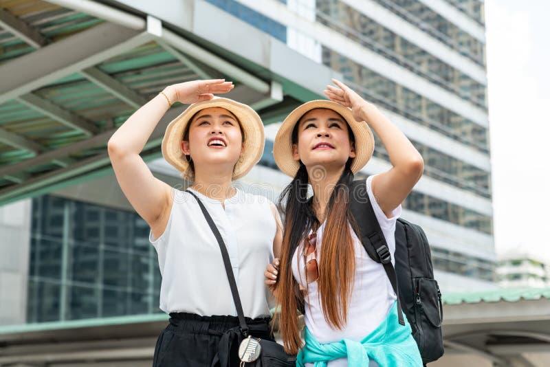Mujeres turísticas asiáticas jovenes que miran en distancia y que llevan a cabo las manos en las frentes foto de archivo libre de regalías
