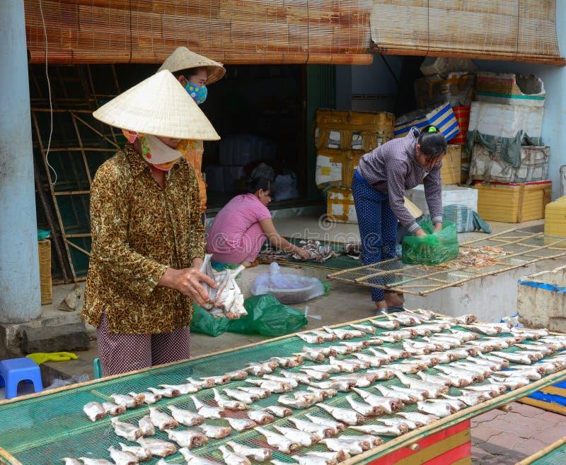 Mujeres vietnamitas que hacen pescados en el mercado fotografía de archivo