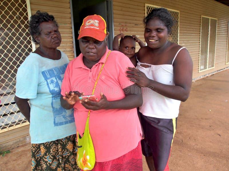 Mujeres y bebé de Tiwi que comprueban el teléfono imagenes de archivo