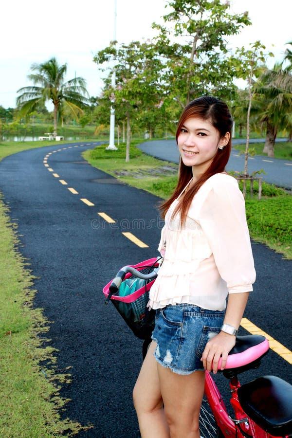 Mujeres y bicicleta asiáticas en el camino imagen de archivo