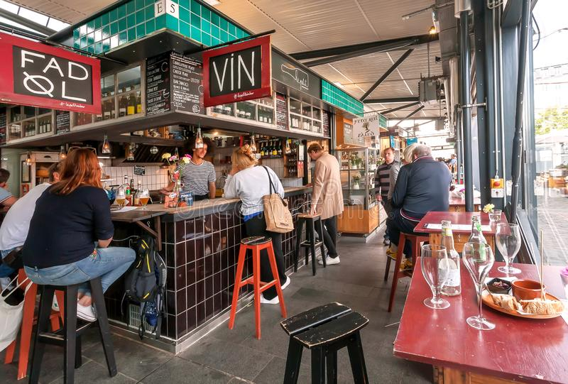 Mujeres y hombres que se divierten y que comen los alimentos de preparación rápida en el mercado de la ciudad con las bebidas y l imágenes de archivo libres de regalías