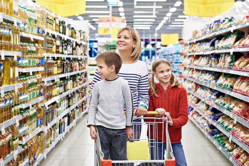Mujeres y niños con compras del carro en supermercado foto de archivo libre de regalías