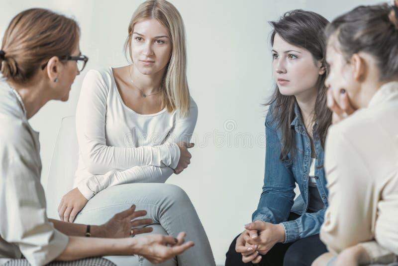 Mujeres y psicólogo que hablan de carrera durante la reunión imagen de archivo libre de regalías
