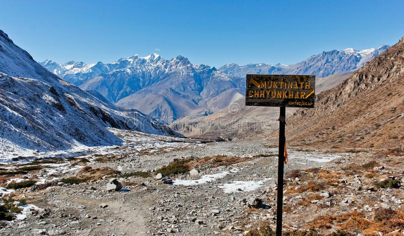 Muktinath village road sign in Himalaya. Valley in summer with snow and ice on tourist trek path stock images