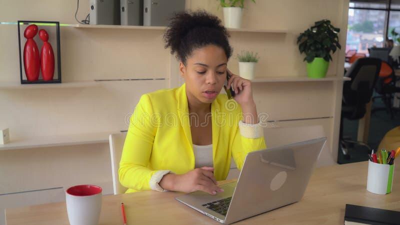 Mulato que usa el ordenador que habla con el cliente imágenes de archivo libres de regalías