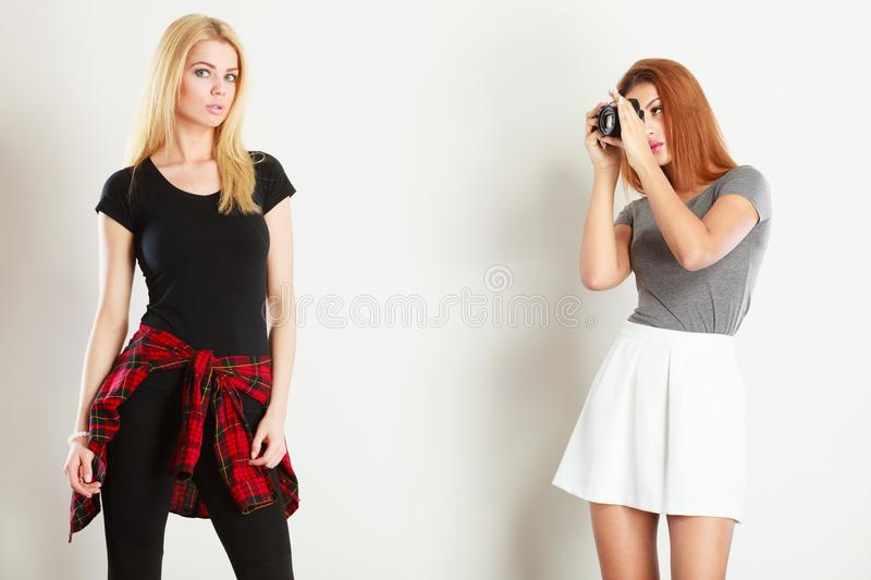 Mulatto girl photographing blonde woman stock photos