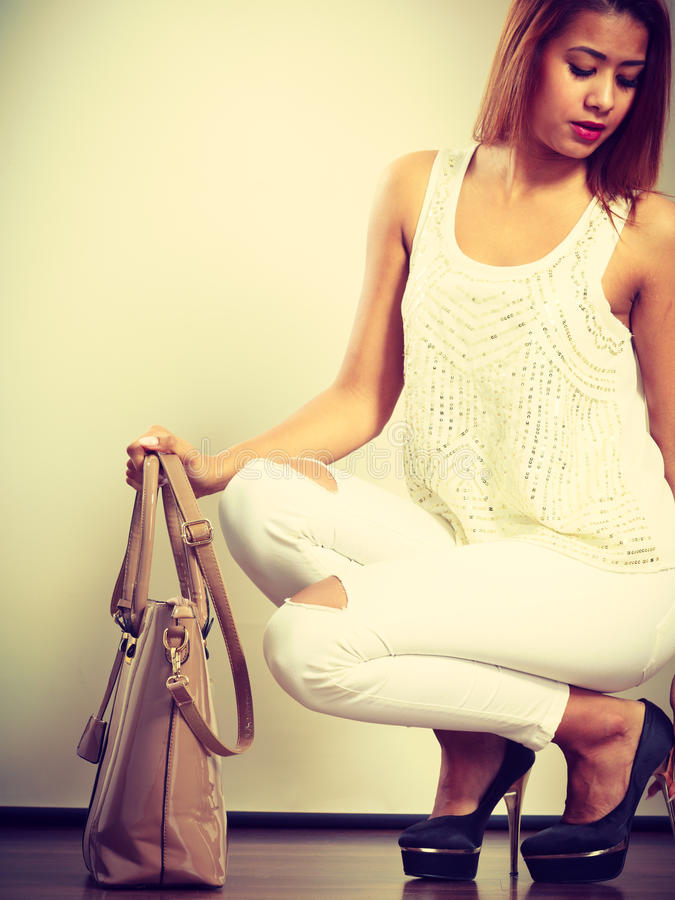 Mulatto woman holding beige leather bag. stock photos