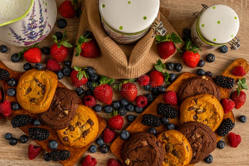 Mulberries, forest fruits and cookies on wooden board stock photo