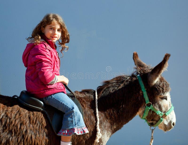 Mule d'âne avec l'équitation de petite fille de gosse heureuse photo stock