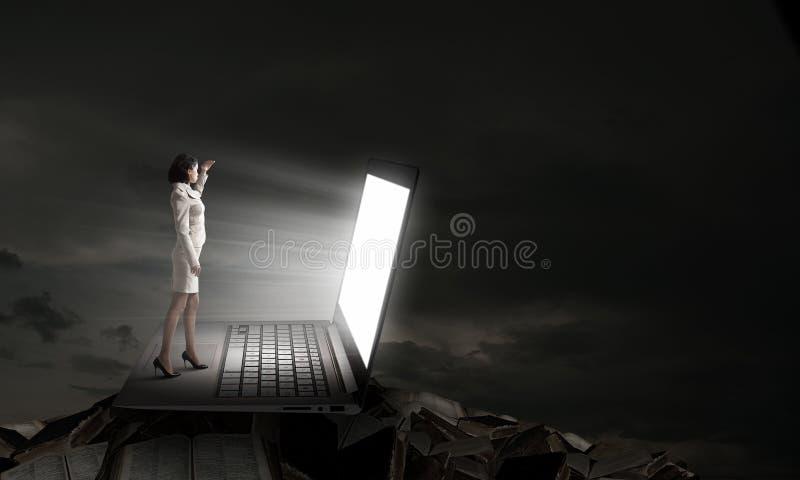 Mulher à luz da tela do portátil foto de stock royalty free