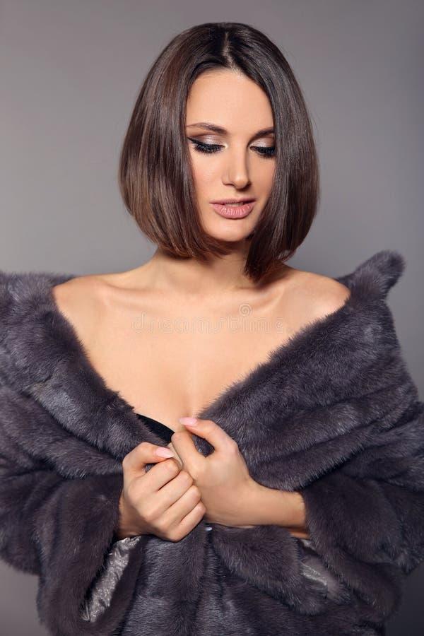 Mulher à moda bonita nova com cabelo curto de Brown no casaco de pele do vison isolado no fundo cinzento do estúdio haircut imagens de stock