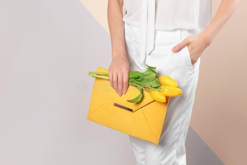 Mulher à moda com as flores da embreagem e da mola contra o fundo da cor, close up imagens de stock royalty free