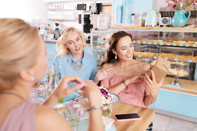 Mulher à moda com a composição agradável que abre sua caixa atual imagem de stock royalty free