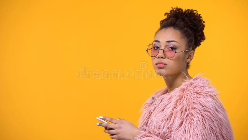 Mulher à moda com o smartphone à disposição que olha desagradado in camera, adolescente fotografia de stock