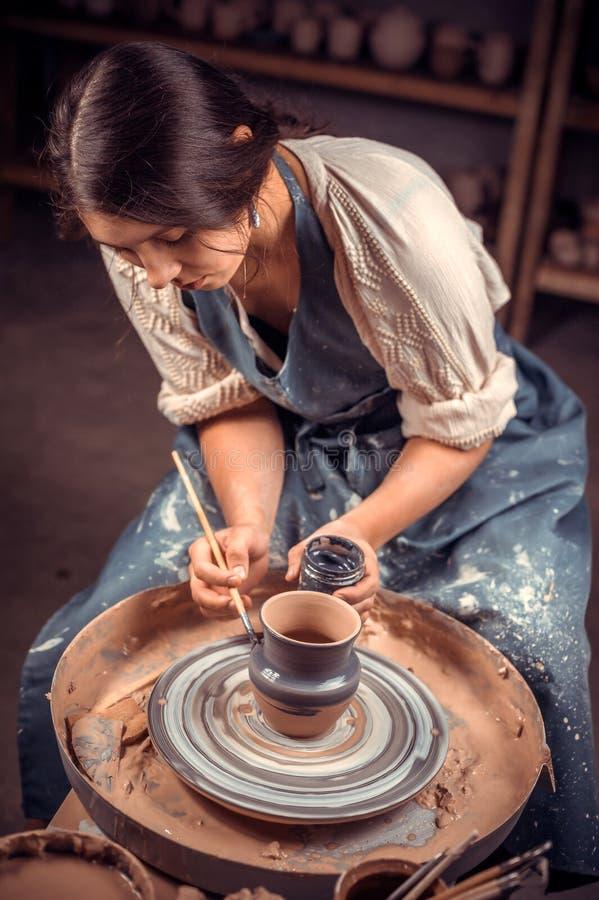 Mulher à moda da cerâmica que situa no banco com roda da cerâmica e que faz o potenciômetro de argila Of?cio nacional fotografia de stock