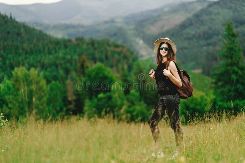 Mulher à moda do moderno com trouxa e no chapéu que sorri no amazi imagem de stock