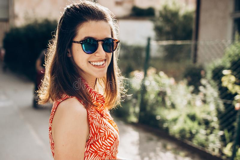 Mulher à moda do moderno que sorri nos óculos de sol e que aprecia o sunshin fotografia de stock royalty free