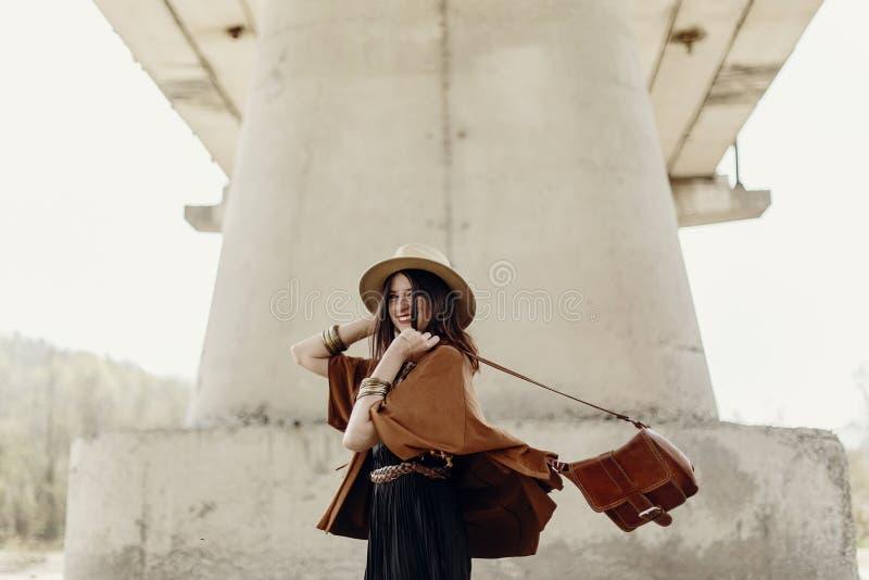 Mulher à moda do moderno que tem o divertimento, no chapéu com cabelo ventoso perto do ri foto de stock royalty free