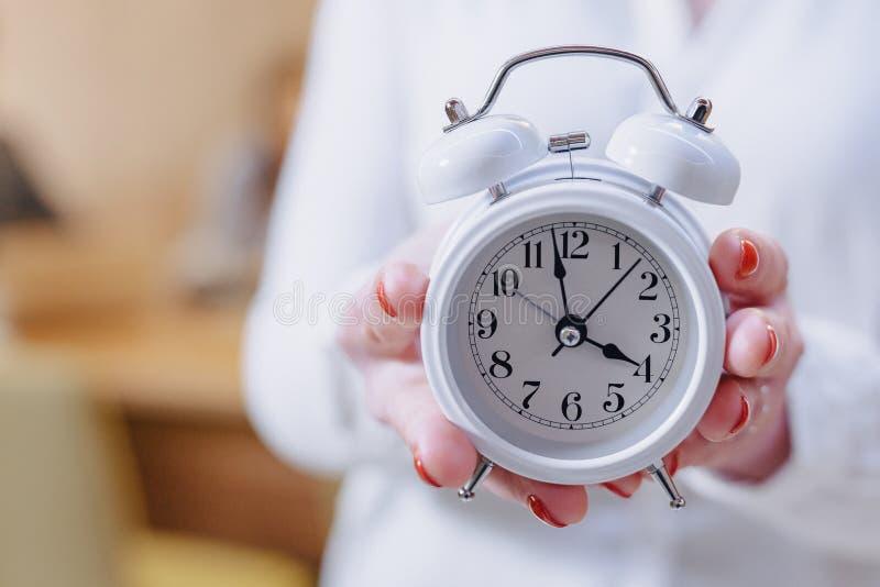 Mulher à moda do trabalhador de escritório nos vidros com um despertador clássico nas mãos no fundo de colegas de trabalho foto de stock
